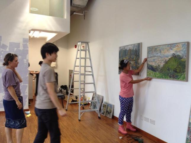 "7 of my ""Urban Landscape"" paintings being hung on the gallery wall"